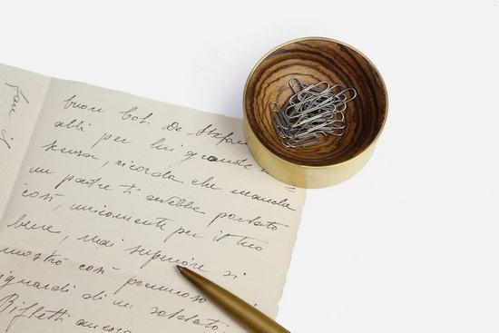 木心置物盒放置在桌面上,绝对是一个吸睛的存在。黄铜的外框,木头里子,形成了一种既强烈又和谐的有趣对比。木头被车削出一个迷人的弧面,木纹也随着弧面而变得灵动多变。 置物盒内置了一颗磁铁,可以吸附住各种铁制小物,如回形针、大头钉等。