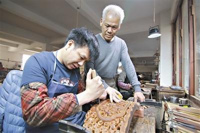 中国侨网胡敏强(右)在指导年轻人雕刻红木。